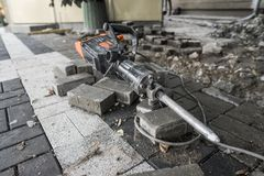 Electric Concrete Breaker laying on a road of cobblestone during sidewalk construction works. Electric Concrete Breaker laying on a road of cobblestone during royalty free stock photos