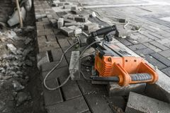 Electric Concrete Breaker laying on a road of cobblestone during sidewalk construction works. Electric Concrete Breaker laying on a road of cobblestone during royalty free stock image