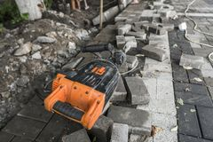 Electric Concrete Breaker laying on a road of cobblestone during sidewalk construction works. Electric Concrete Breaker laying on a road of cobblestone during royalty free stock photography
