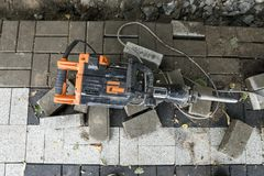 Electric Concrete Breaker laying on a road of cobblestone during sidewalk construction works. Electric Concrete Breaker laying on a road of cobblestone during stock photo
