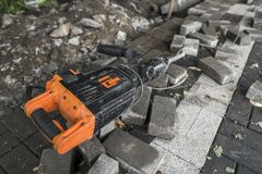 Electric Concrete Breaker laying on a road of cobblestone during sidewalk construction works. Electric Concrete Breaker laying on a road of cobblestone during stock image