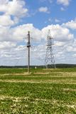 Electric concrete pole. Concrete and metallic electric poles with a large number of wires installed on a field with green vegetation, a summer landscape with a stock image