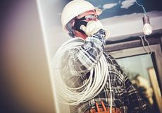 Electric Contractor Job. Professional Electrician Making Phone Conversation with Investor Stock Image
