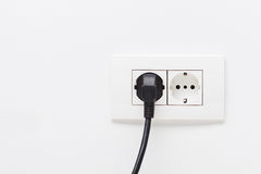 Electric cord plugged into an electricity socket. Black electric cord plugged into a white electricity socket on white background stock photos