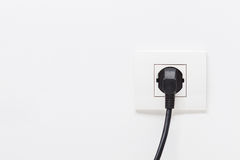 Electric cord plugged into a single electric socket Royalty Free Stock Photo