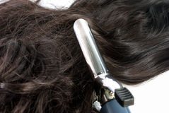 Electric curling iron and hair Royalty Free Stock Image