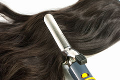 Electric curling iron and hair Royalty Free Stock Photo