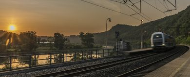 Electric double deck train with sunrise. In Uholicky village Royalty Free Stock Photography