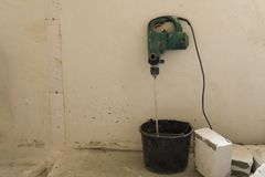 The electric drill in the bucket with cement for gas blocks laying royalty free stock photos