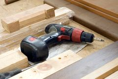 Electric drill closeup. A carpenter's tool closeup, an electric drill and a screwdriver, some pieces of wood on a table Royalty Free Stock Photo