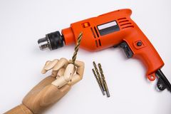 Electric drill. Orange electric drill with handle on white background. Arm holding a drill Stock Images