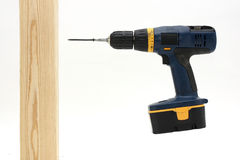 Electric drill about to screw into wood Stock Photo