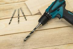 Electric drill on a wooden background. Carpentry tools stock photography