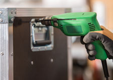 Electric drill in workshops. Hands hold electric drill in workshops Royalty Free Stock Photo
