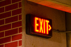 Electric exit sign on brick concrete wall at night. Glowing electrical exit sign mounted on a brick concrete wall at night in a dark corner of a corridor Stock Photography