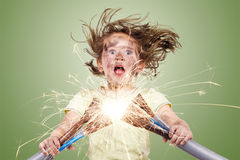 Electric failure. Kid holding electric wires on green background royalty free stock photo