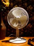 Electric Fan. A small electric fan standing on a table in a patch of sunlight Royalty Free Stock Photography
