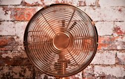 Electric fan - air conditioner. Capture of old style brass or copper effect electric fan - ventilator with moving blades on brick wall background stock photos