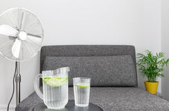 Electric fan and water to cool down. Electric fan near armchair, and some water to cool down Royalty Free Stock Images