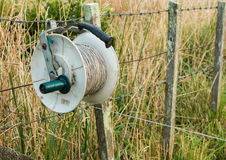 Electric Fence Reel. One used electric fence reel hooked on a fence Stock Photos