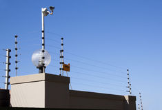Electric Fence and Security Camera Atop Boundary Wall Royalty Free Stock Photo