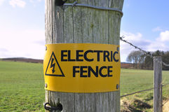 Electric Fence Sign in the Countryside. A sign warning of an electric fence in a rural, countryside location Royalty Free Stock Photo