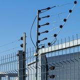 Electric fence. View of an electric fence installation on a metallic grilled fence Royalty Free Stock Photo