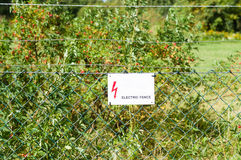 Electric fence with warning sign to prevent shock Royalty Free Stock Photos
