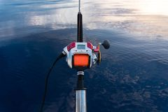electric fishing reel mounted on a rod with sea in the background and orange line stock photo