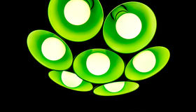 Electric fixture with round plafonds from glass. Bright modern green emerald chandelier with seven round plafonds with lamps inside them against black background Royalty Free Stock Photography