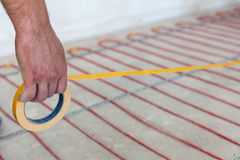 Electric floor heating system installation in new house Stock Image
