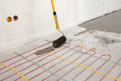 Electric floor heating system installation in new house. Closeup of concrete, roller and red electrical wires. Stock Photo