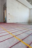 Electric floor heating system installation in new house. Room with white walls, cement and electrical wires.  Stock Image