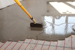 Electric floor heating system installation in new house. Worker align cement with roller. Royalty Free Stock Photos