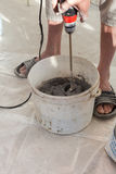 Electric floor heating system installation in new house. Worker use concrete hand mixer to prepare cement. Stock Photos