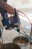 Electric floor heating system installation in new house. Worker use concrete hand mixer to prepare cement. Royalty Free Stock Photography