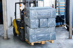 Electric forklift carries boxes. Cargo packed in polyethylene film gray Stock Photo