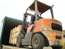 Electric Forklift Loading Cargos into Container Stock Image
