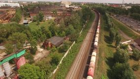Electric freight train, locomotive moves rides by rail with wagons, transportation, deliver barrel, petrol, oil tank. Transports cargo in city, town. Aerial stock video footage