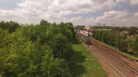 Electric freight train, locomotive moves rides by rail with wagons, transportation, deliver container, transports cargo. In city, town. Aerial view, drone, air stock video