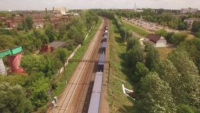 Electric freight train, locomotive moves rides by rail with wagons, transportation, deliver container, transports cargo. In city, town. Aerial view, drone, air stock footage