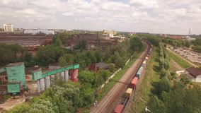 Electric freight train, locomotive moves rides by rail with wagons, transportation, deliver container, transports cargo. In city, town. Aerial view, drone, air stock video footage