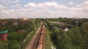 Electric freight train, locomotive moves rides by rail with wagons, transportation, transports wood, timber, logs. Deliver container, transports cargo in city stock video