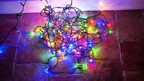 Electric garland on the floor. An electric garland that lights up and turns off in all colours is placed in disorder on the floor stock video