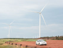 Electric generating windmills. Some hydro generating wind mills on the top of the cliffs of Prince Edward Island, Canada with it's red sand and a white car to royalty free stock images