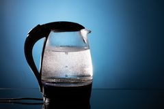 Electric glass kettle on blue background royalty free stock photos