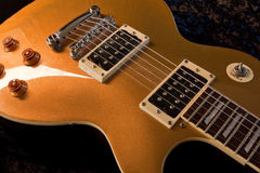 Electric Gold. A gold electric guitar shot in the studio against a black background Royalty Free Stock Images