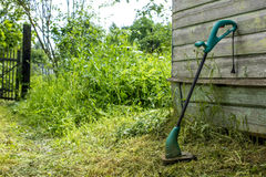 Electric grass trimmer stands in the garden near the house Royalty Free Stock Image