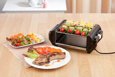 Electric grill stove with barbecue and steak. Display on wooden table Stock Photos