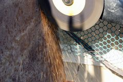 Electric grinding wheel on the steel structure, Bulgarian close-up. Sparks from the grinder royalty free stock image